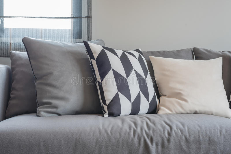 Black and white pillows on modern grey sofa stock image for Canape noir quel coussin