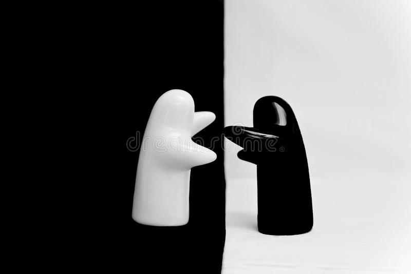 Black and white porcelain figurines on a white/black background. Hugging royalty free stock photos
