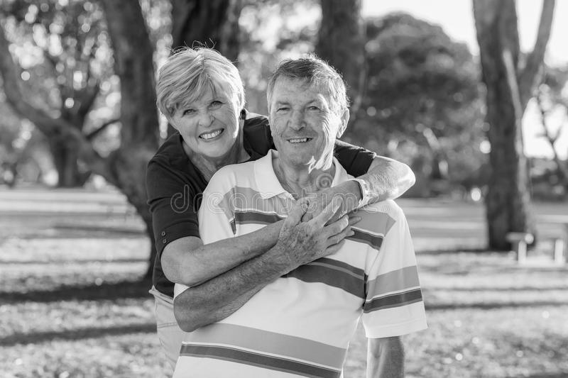 Black and white portrait of American senior beautiful and happy mature couple around 70 years old showing love and affection smili. Ng together in the park stock photo