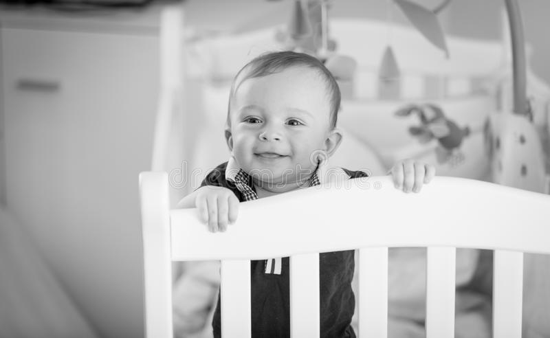 Black and white portrait of baby boy standing at his crib stock photography