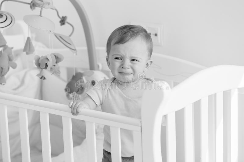 Black and white portrait of baby standing in crib and crying stock photography