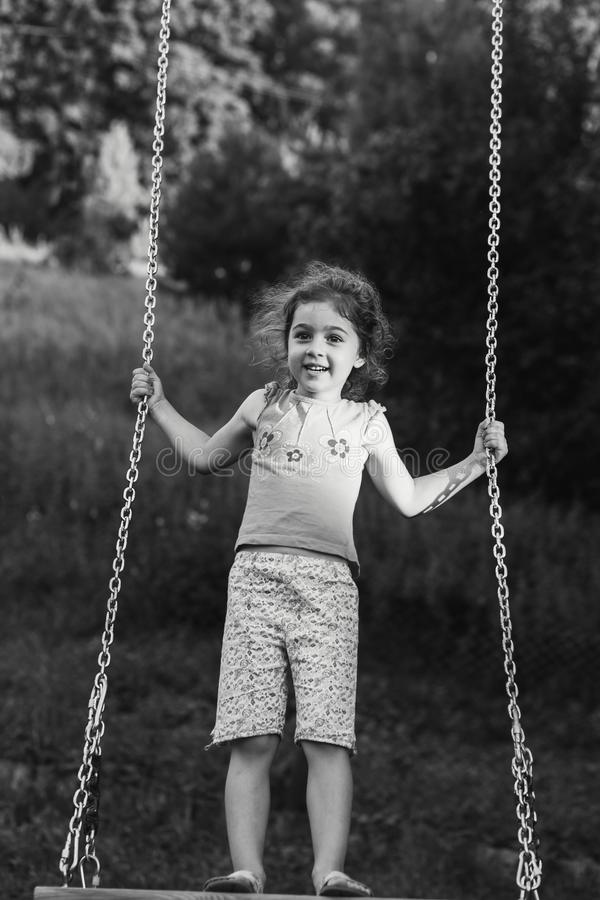 Black and white portrait of Cute little girl smiling on swing at summer day, Happy childhood concept stock image