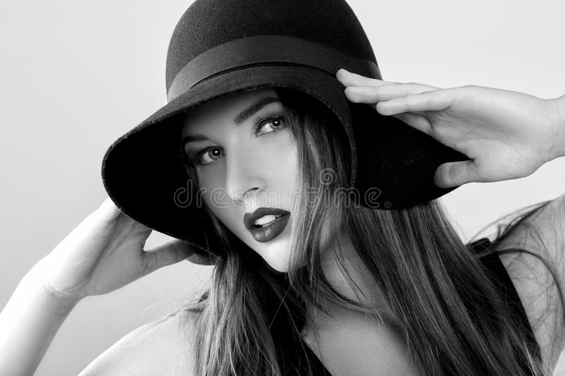 Black and white portrait of beautiful woman in black hat royalty free stock image