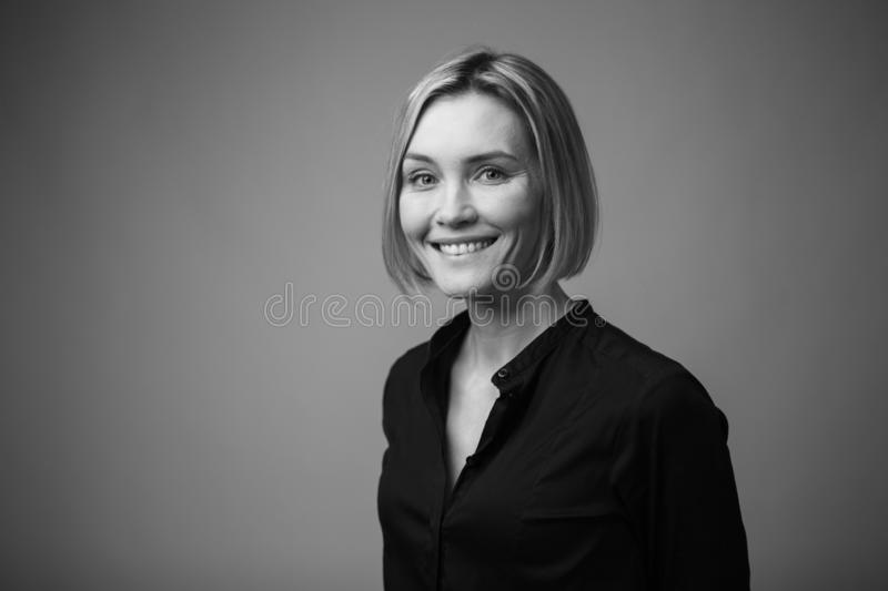 Black and white portrait of a beautiful smiling woman on a dark background royalty free stock photo