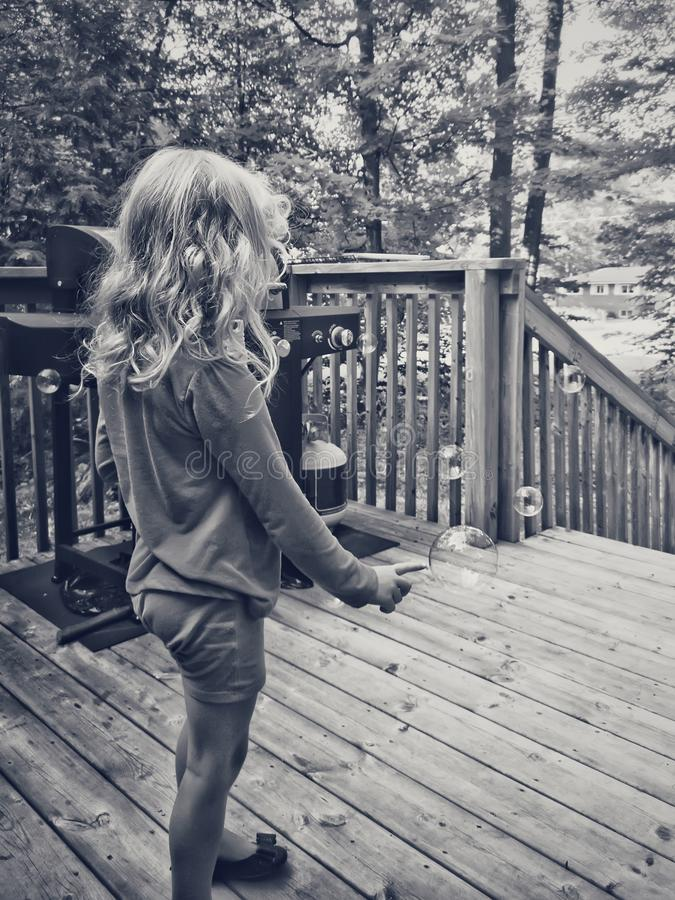 Black and white portrait of blonde preschool girl popping soap bubbles royalty free stock photos
