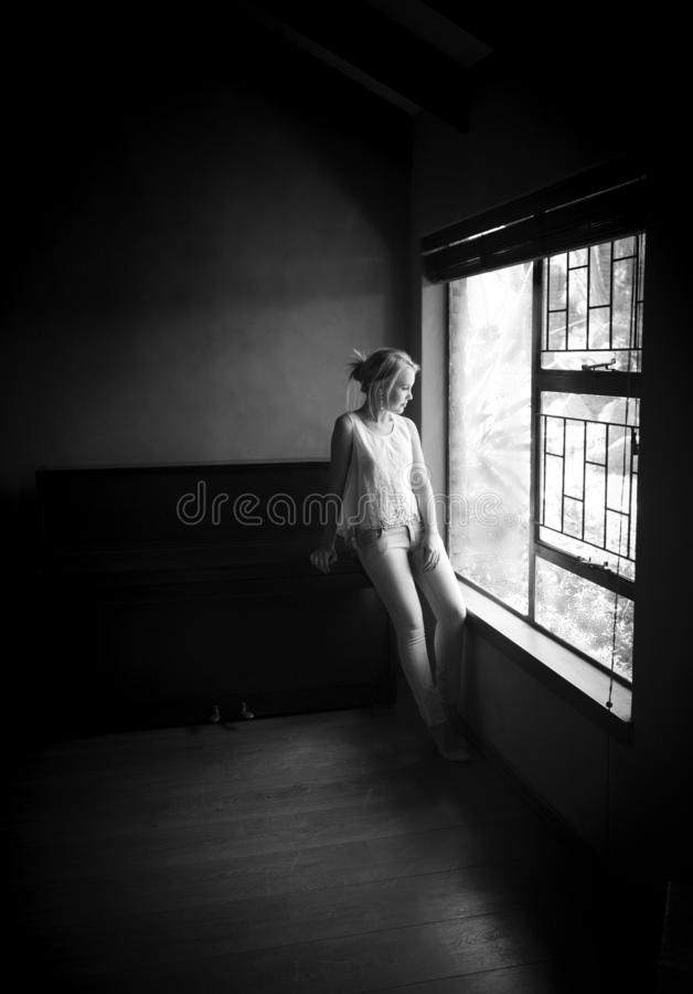 Black and white portrait of blonde woman posing next to a window with natural light royalty free stock image