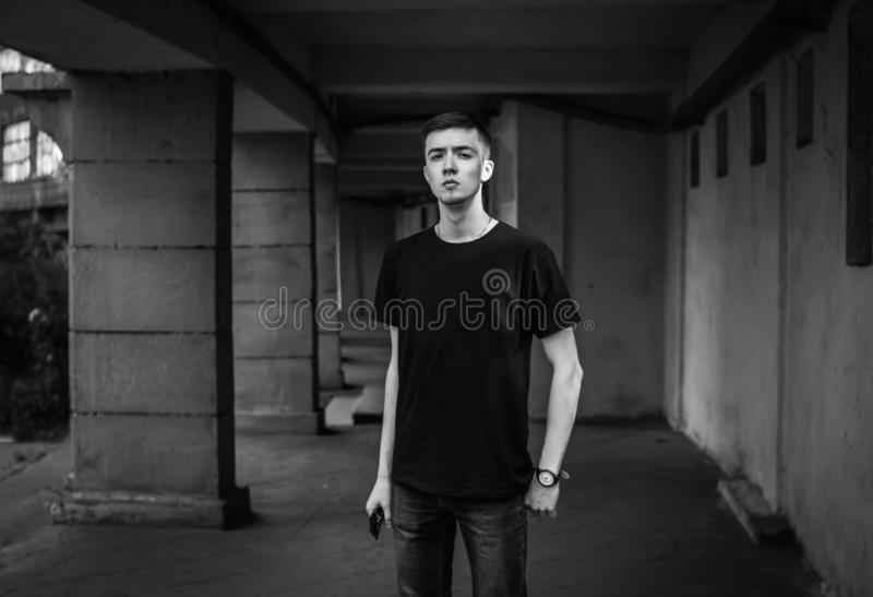 Black and white portrait of confident handsome young man standing near old building royalty free stock photos