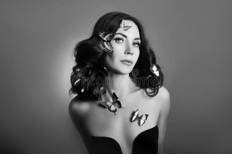 Black and white portrait of a girl with butterflies on her face closeup. Beautiful brunette woman and butterfly.  royalty free stock photography