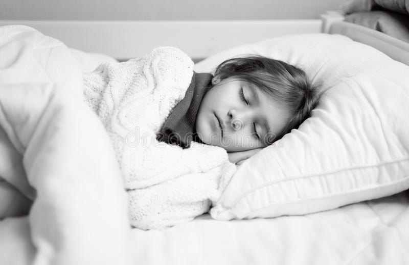Black and white portrait of girl in sweater sleeping in bed stock photo