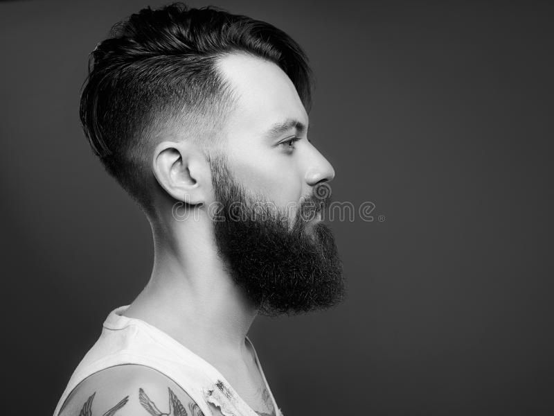 Black and white portrait of handsome man with beard and tattoo. Bearded hipster boy in vintage torn dirty shirt royalty free stock images