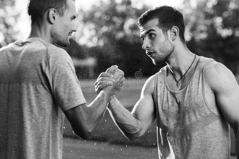 Black and white portrait of handsome men with arm wrestling. Black and white portrait of two young handsome men with arm wrestling royalty free stock images