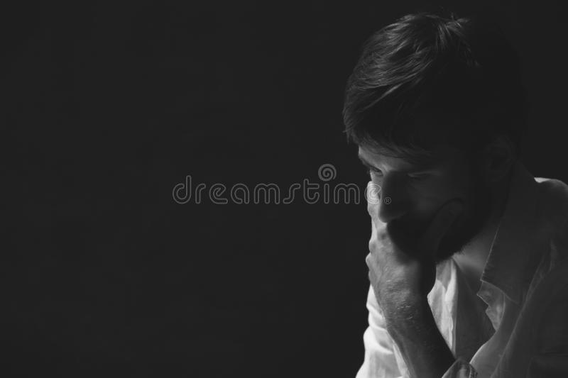 Black and white portrait of worried man, photo with copy space on dark background stock image