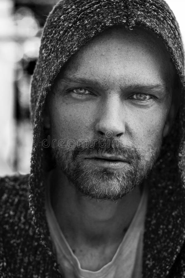 Black and white portrait of man with beard wearing a hoodie and looking at the camera royalty free stock image