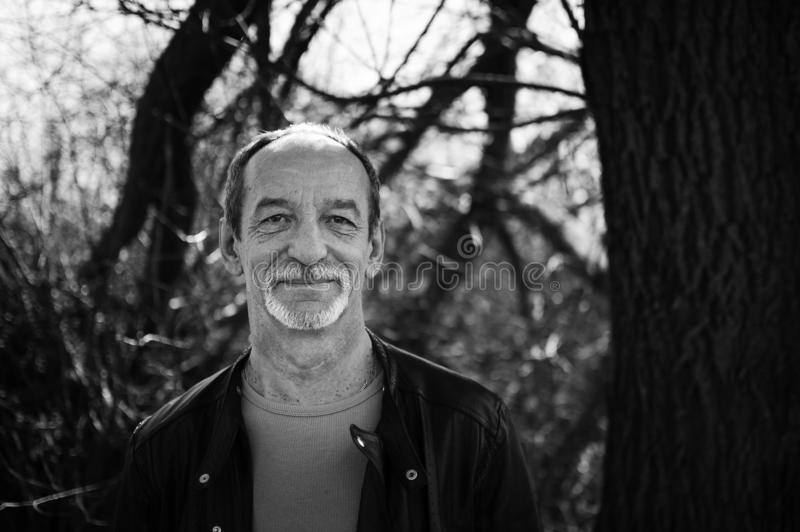 Black and white portrait of mature serious man with grey hair in dark leather jacket standing outdoors near the tree on stock images