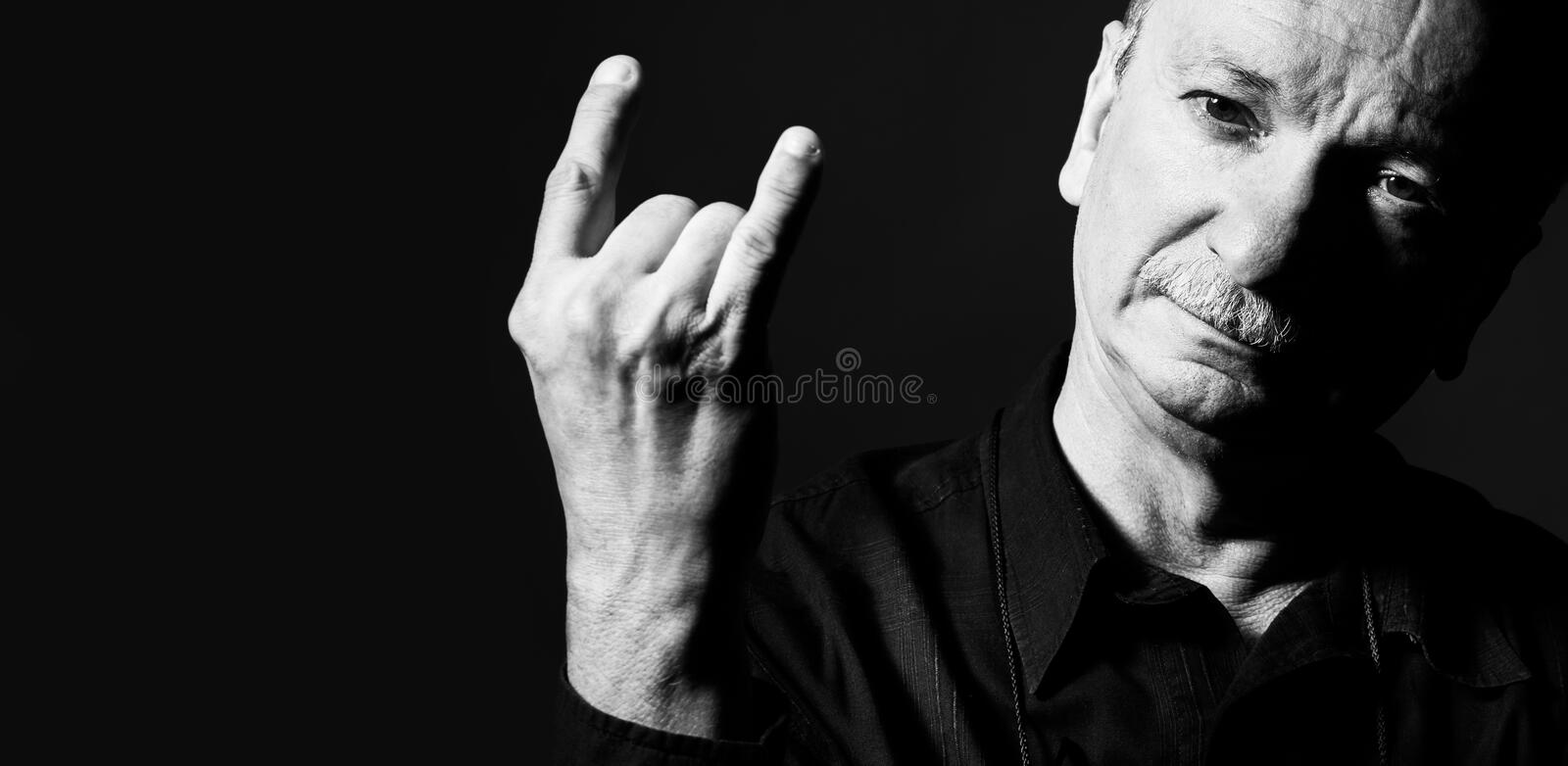 Black and white portrait of an old man. Gesturing on dark background with copy space. Elderly old man shows with fingers horns. Horns rock sign symbol gesture stock photography