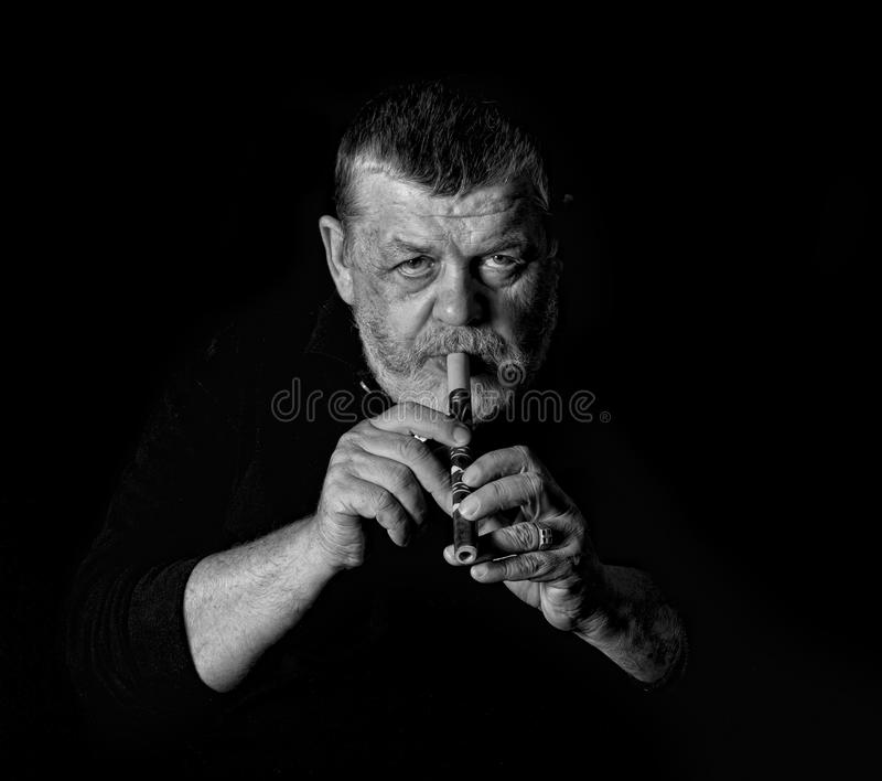 Black and white portrait of old musician. Playing Ukrainian woodwind instrument sopilka royalty free stock photos