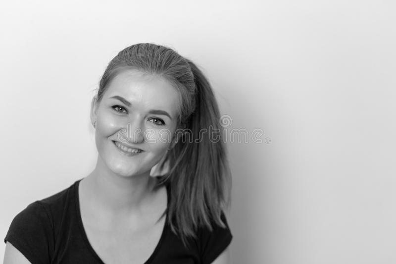 A black and white portrait of a positive and happy beautiful girl royalty free stock photography