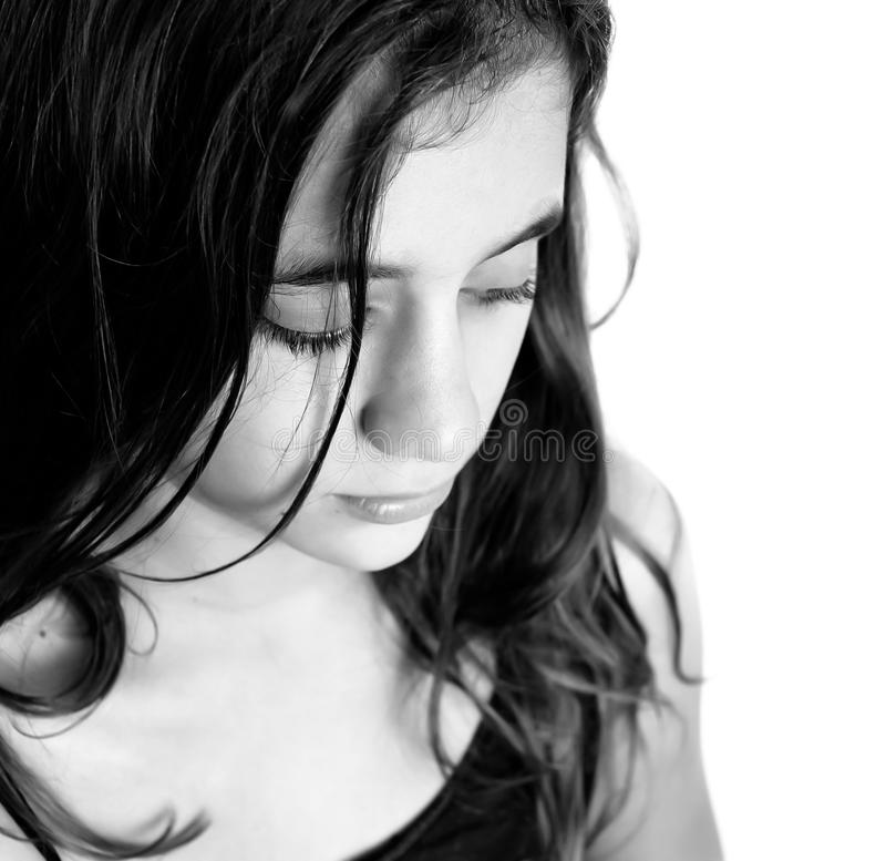 Black and white portrait of a sad hispanic girl. Black and white portrait of a beautiful sad hispanic girl isolated on a white background with space for text stock image