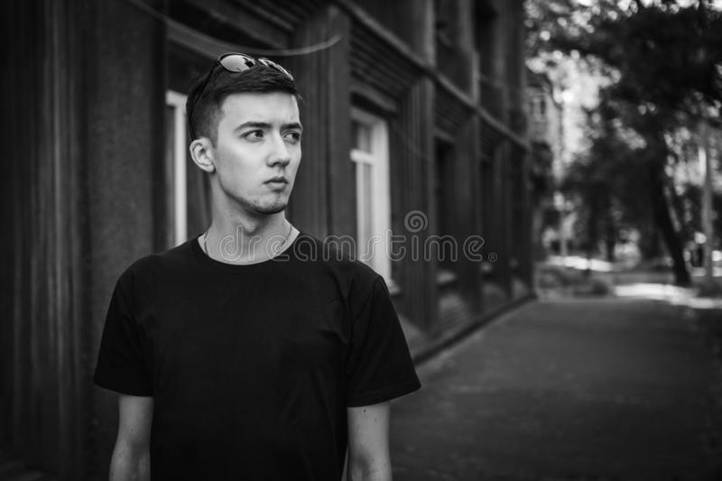 Black and white portrait of sad and pensive handsome young man standing near old building stock photo