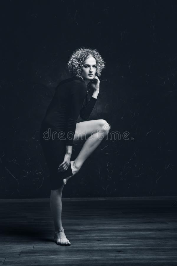 Black and white portrait of a sad transgender guy model with blue eyes and blond hair in the image of a woman an afro hair, stock photo