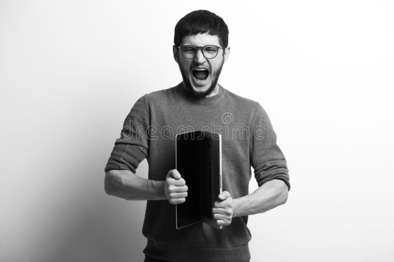 Black and white portrait of screaming young man opening laptop stock image