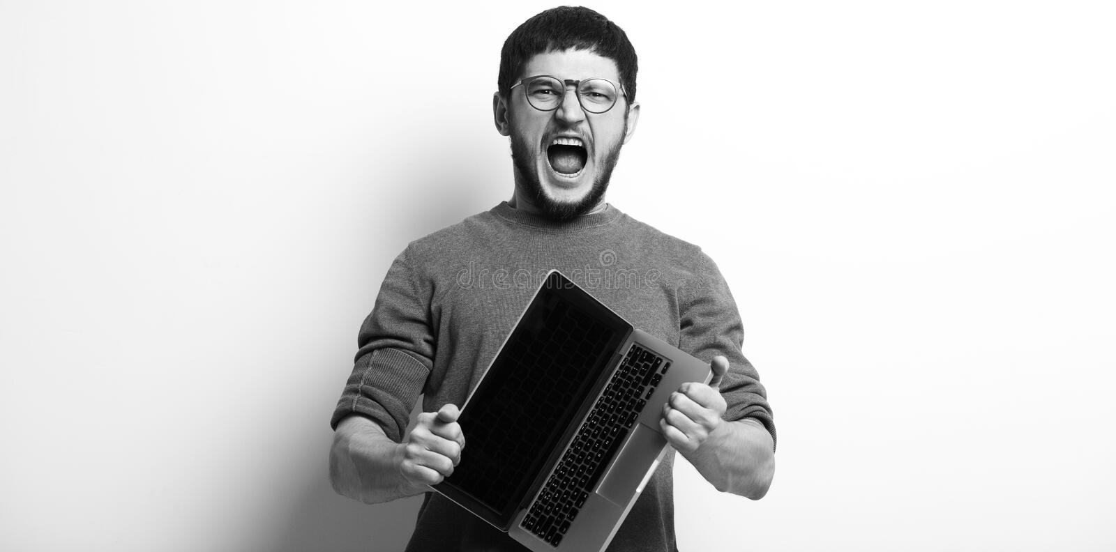 Black and white portrait of screaming young man opening laptop stock photo