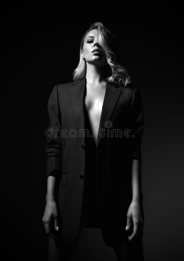 Self-confident impudent young blonde woman in formal jacket over her naked body is standing with her head high up. Black and white portrait of self-confident stock photography
