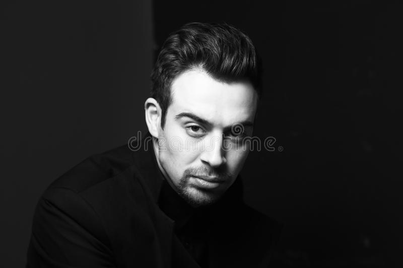 Black and white portrait of a serious young handsome man dressed in black, dramatic lighting stock images