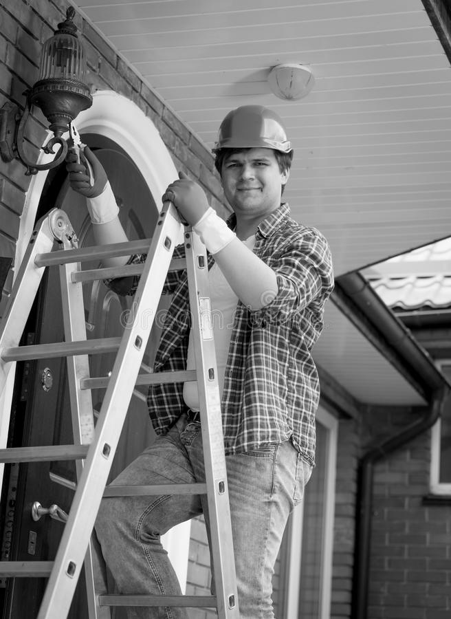 Black and white portrait of smiling electrician posing on top of royalty free stock image