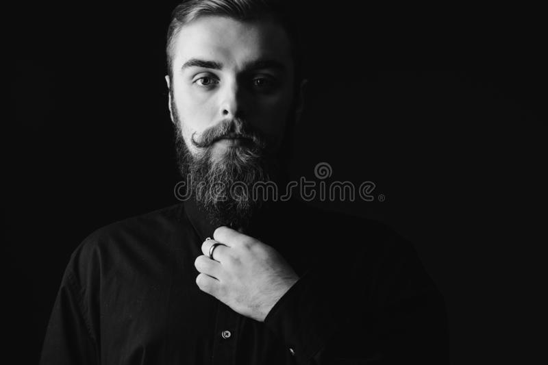 Black and white portrait of a stylish man with a beard and stylish hairdo dressed in the black shirt on the black royalty free stock photos