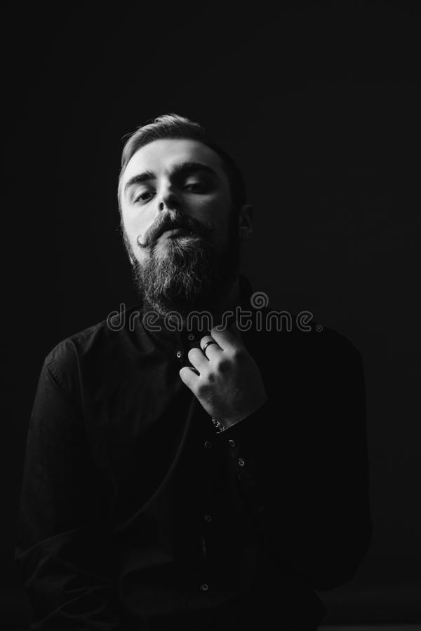 Black and white portrait of a stylish man with a beard and stylish hairdo dressed in the black shirt on the black royalty free stock image