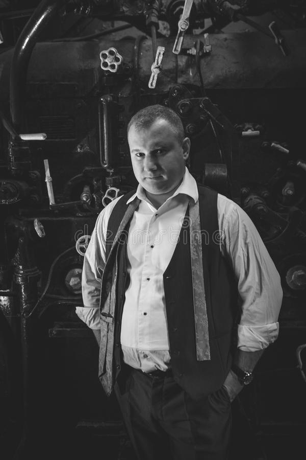 Black and white portrait of stylish man in retro suit at furnace. Black and white portrait of stylish man in retro suit at coal furnace stock photo