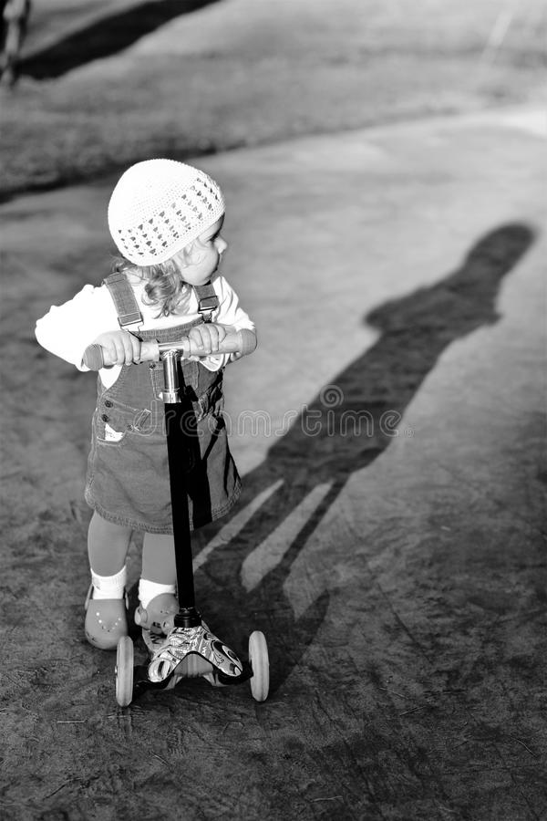 Black and white portrait of a stylish one year old girl riding a scooter and her shadow stock photos
