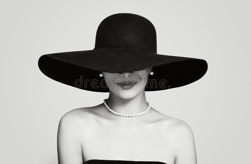 Black and white portrait of vintage woman in classic hat and pearls jewelry, retro styling girl.  royalty free stock image