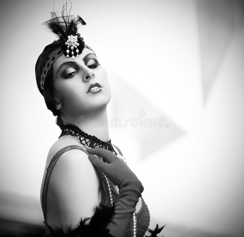 Black and white portrait of a woman from 1920s. Black-and-white retro style depiction of a woman in typical style of the 1920s or 1930s. She's fashionably royalty free stock image