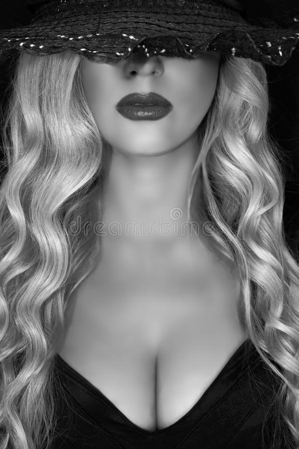 Black and white portrait of young blonde woman in black hat with black hat decollete and lush breasts, on a black background. royalty free stock photo