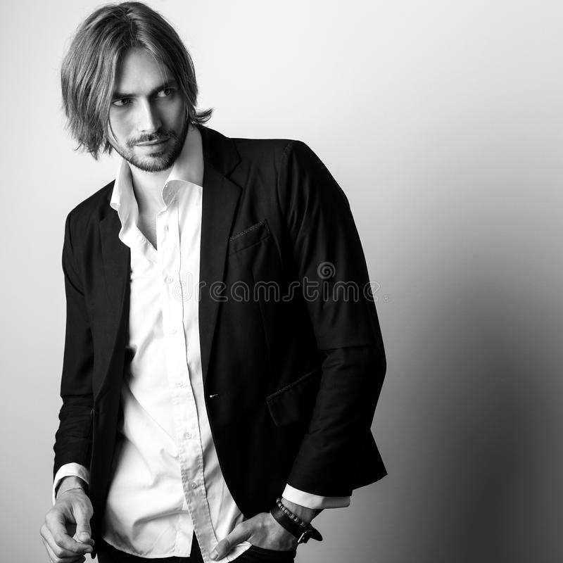 Black-white portrait of young handsome long hair man against studio background royalty free stock photo