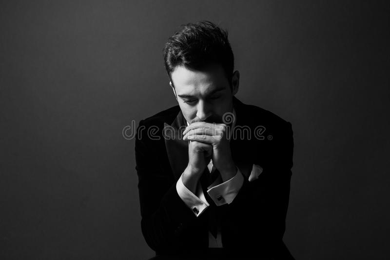 Black and white portrait of a young handsome man in a suit, upset, hands together covering mouth stock images