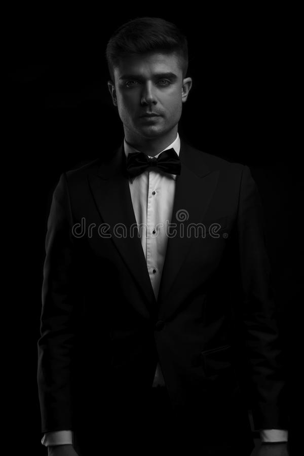 Black and white portrait of young man in tuxedo. Standing on black background royalty free stock photography
