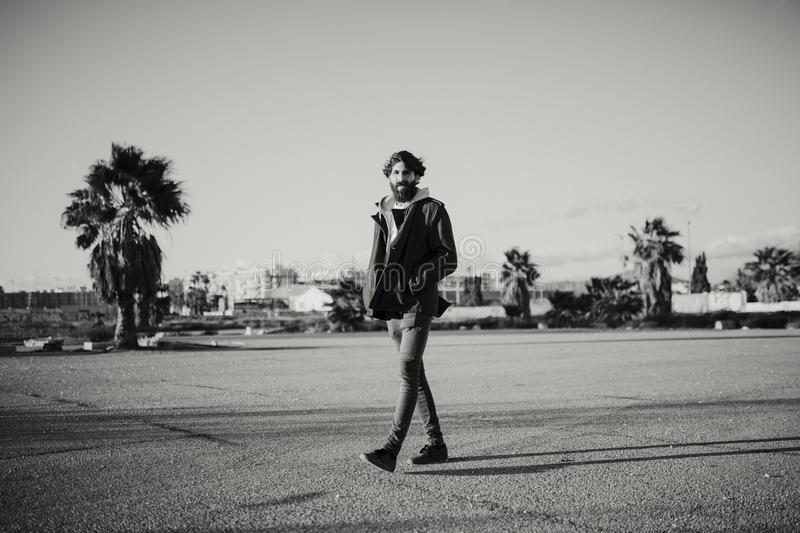 Black and white portrait of young man walking outdoors at sunset with urban clothes style. royalty free stock images
