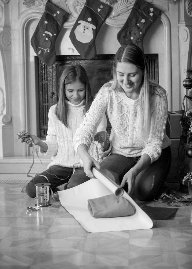 Black and white portrait of young mother with daughter wrapping stock photo