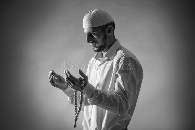 Black and white portrait of young Muslim man praying on dark background stock photography