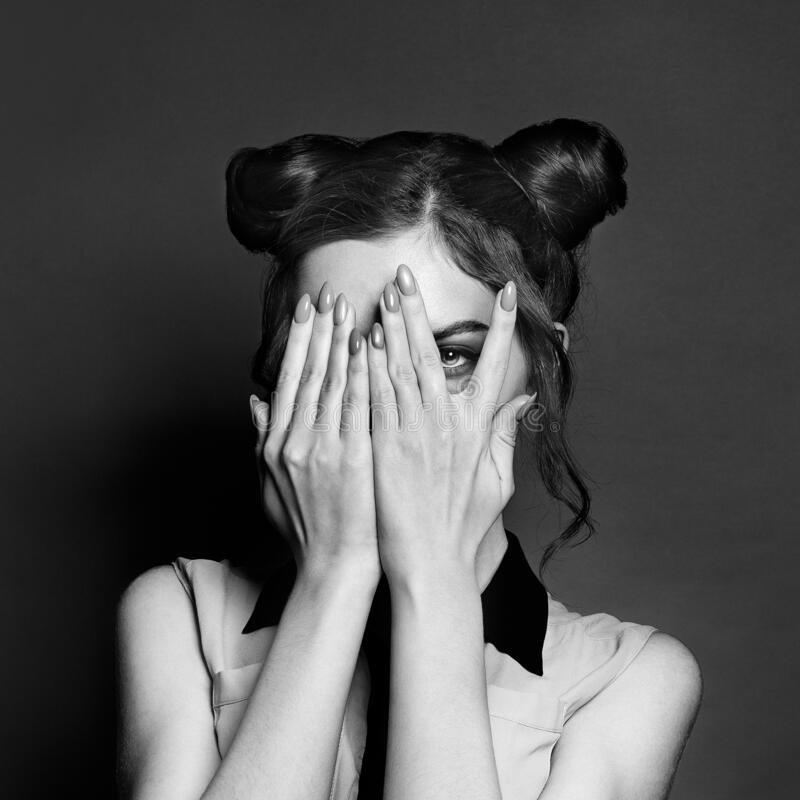 Black and white portrait of young woman hiding behind her hands and looking at camera.  royalty free stock images