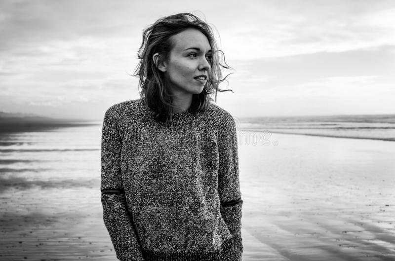 Black and white portrait of a young woman standing on a windy beach stock photo