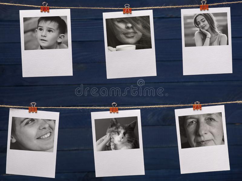 Black and white portraits of people hanging on a linen thread on stationery clips on a a blurred wooden dark blue background, stock photos