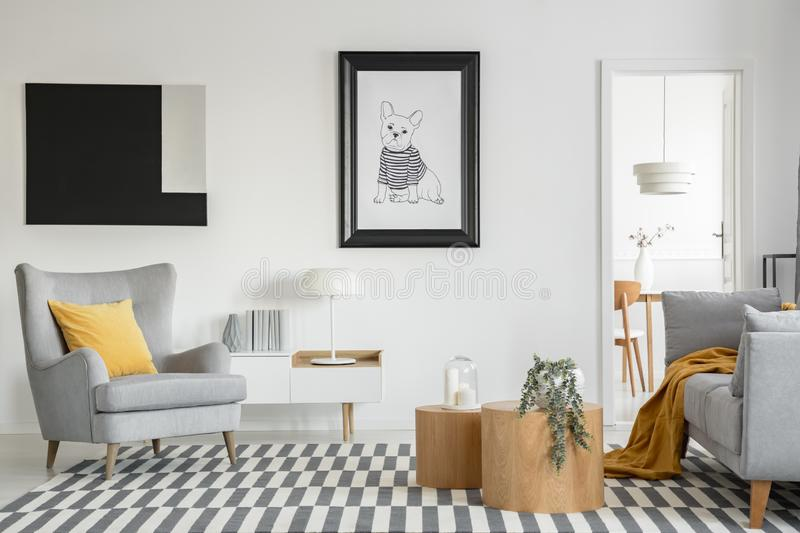 Black and white poster of dog on the wall of fashionable living room interior with two wooden coffee tables with flowers stock photography