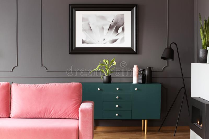 Black and white poster hanging on molding wall in dark living room interior with green cupboard with plant and vases, metal lamp. Black and white poster hanging royalty free stock images
