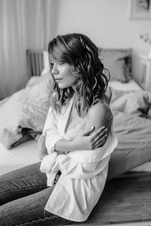 Black and white prtrait of a cute tender girl in a man shirt and white underwear is dreaming on her bedroom stock photography