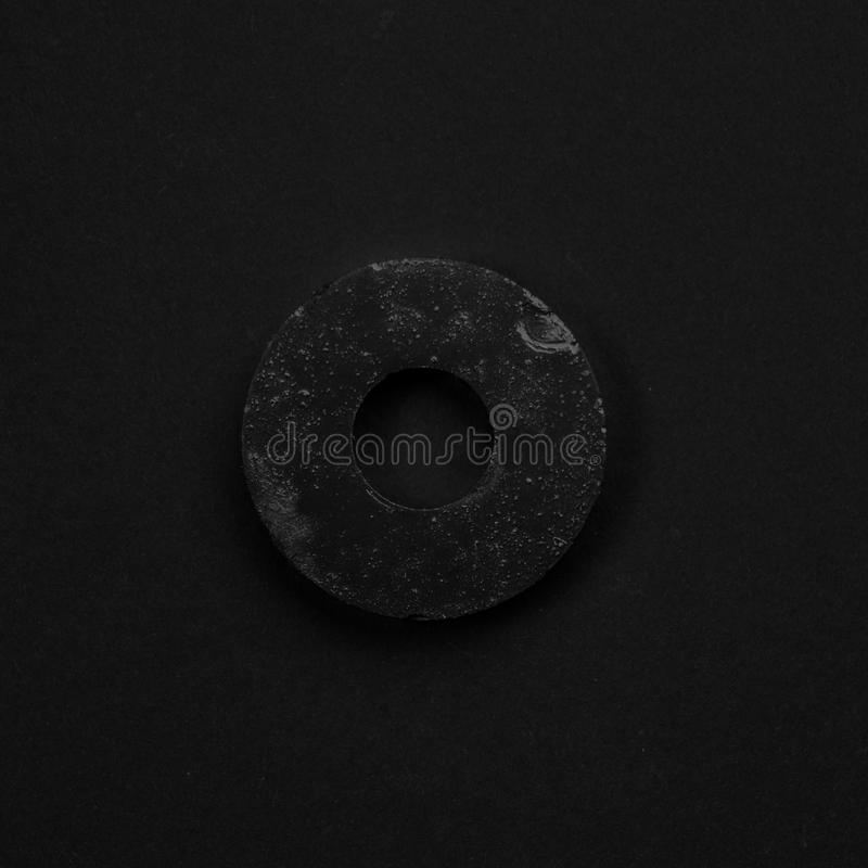 Black & white puck gasket isolated on black background. Symbolic repair tool stock photos
