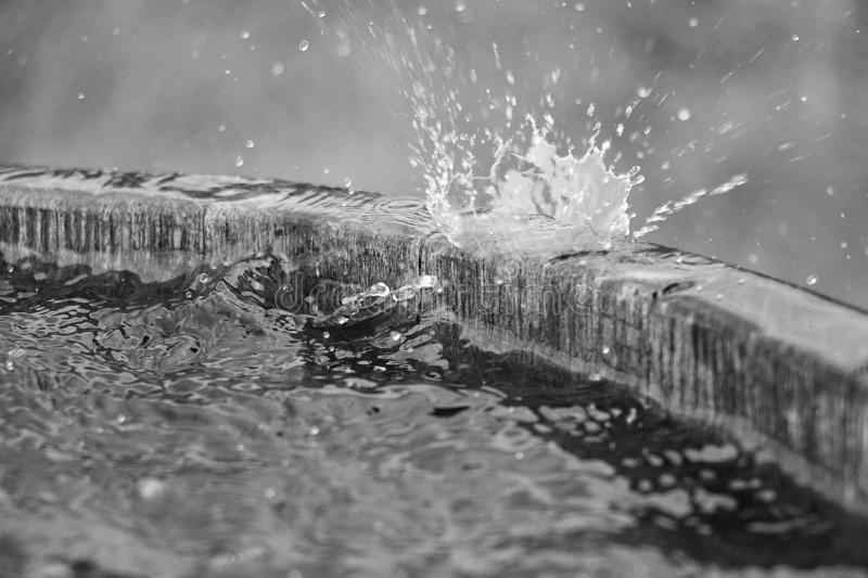 Black and white of rain is falling in a wooden barrel full of water in the garden. Black and white of rain is falling in a wooden barrel royalty free stock photos